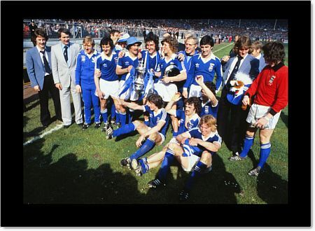 Football - 1978 FA Cup Final - Ipswich Town 1 Arsenal 0 Ipswich players Mick Mills, Brian Talbot and Clive Woods hold the FA Cup trophy as the team celebrate, with manager Bobby Robson, left, on the Wembley pitch