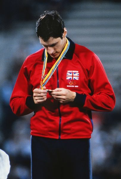 Allan Wells inspects his 100m gold medal on the podium at the 1980 Moscow Olympics
