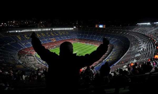 An Arsenal fan sings and dances in the top tier of the Nou Camp before the game against Barcelona