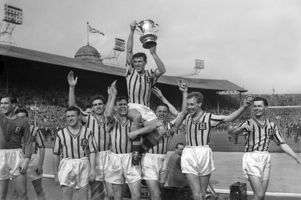 Football - 1956 / 1957 FA Cup - Final: Aston Villa 2 Manchester United 1 Aston Villa captain Johnny Dixon lifts the trophy on his teammates shoulders after victory at Wembley. From left to right, Leslie Smith, Pat Saward, Peter Aldis, Dixon with trophy
