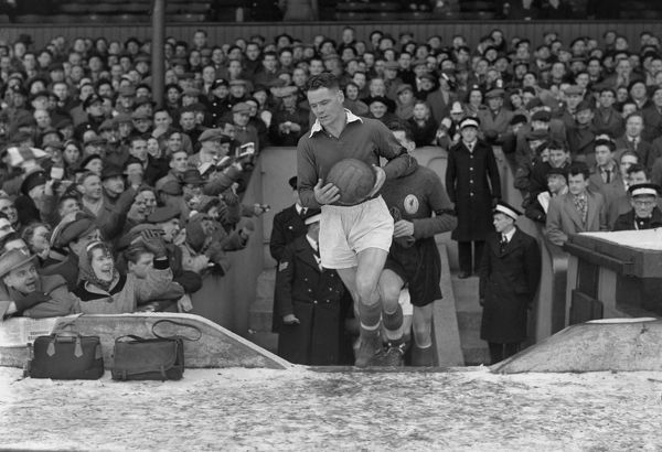Football - 1955 / 1956 FA Cup - Fifth Round Replay: Liverpool 1 Manchester City 2 Billy Liddell of Liverpool is applauded onto the pitch by the Liverpool supporters at Anfield. 22/02/1956