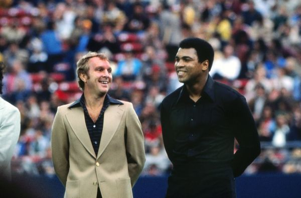 Football England Footballer Bobby Moore and boxer Muhammad Ali (then the World Heavyweight Champion) share a laugh before Pele's last game. Pele's farewell game. Cosmos v Santos, Giants Stadium, New York, 01/10/1977