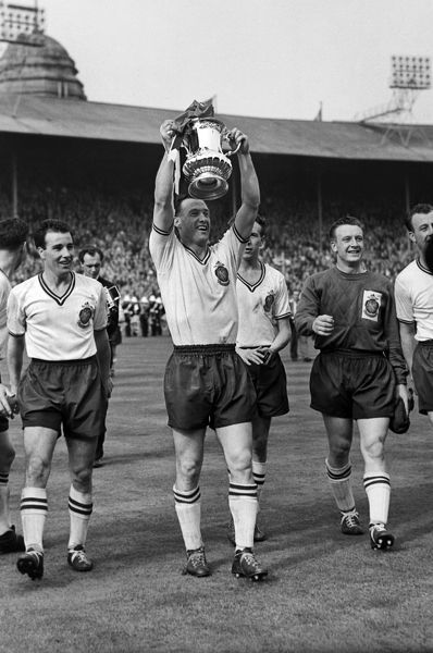 Nat Lofthouse (Captain) Bolton Wanderers holds aloft the trophy. Eddie Hopkinson (right) and Bryan Edwards (left). 03/05/1958 Bolton Wanderers v Manchester United FA Cup Final 1958. Credit: Colorsport