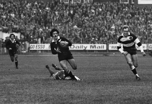 Rugby Union - 1972 / 1973 New Zealand Tour of Great Britain & France - Barbarians 23 New Zealand 11 Bryan Williams breaks past a grounded Mike Gibson and past the pursuing David Duckham to set up Grant Batty for the first All Black try at Cardiff