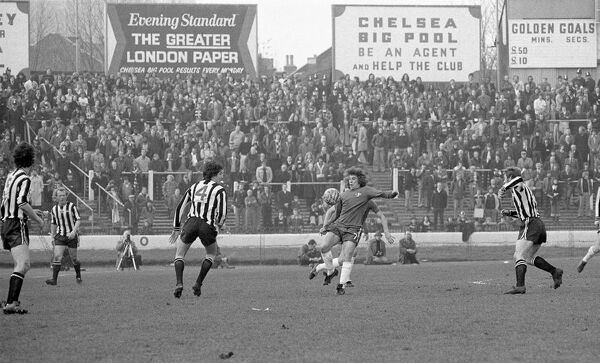 Football - 1974 / 1975 First Division - Chelsea 3 Newcastle United 2    Chelsea's Ian Britton on the ball, surrounded by Newcastle players including Jim Smith (#4), at Stamford Bridge.    Large advertising hoardings are seen in the background above the stand