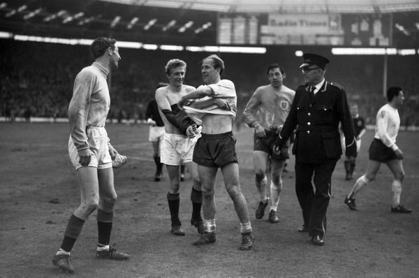 Football BOBBY CHARLTON (ENGLAND) EXCHANGES SHIRTS WITH DENIS LAW (SCOTLAND) A FELLOW MANCHESTER UNITED PLAYER, AFTER THE MATCH.  Bill Brown (Scotland goalkeeper) left.  ENGLAND V SCOTLAND 1965 10/04/1965.  Wembley Stadium CREDIT: COLORSPORT