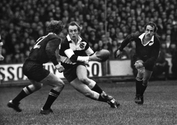 Rugby Union - 1972 / 1973 New Zealand Tour of Great Britain & France - Barbarians 23 New Zealand 11 David Duckham of the Barbarians dummies Ian Hurst (#12) of the All Blacks for a break at Cardiff Arms Park. All Blacks fly-half Bob Burgess behind