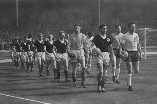 Football Jimmy Armfield (England) and Eric Caldow (Scotland) lead out their teams followed by Bill Brown and Denis Law.  England v Scotland 1963. Wembley  06/04/1963.  Credit : Colorsport