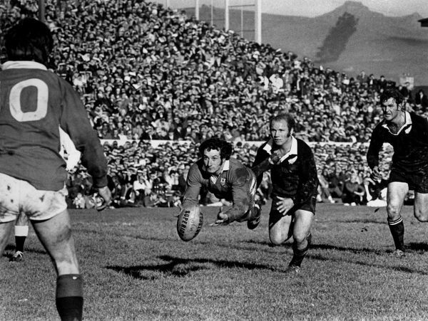 Gareth Edwards passes to Barry John (10, Lions) under pressure from Syd Going as Ian Kirkpatrick (All Blacks) closes in. New Zealand v British Lions. 2nd Test, 1971. Credit: Colorsport /Bush