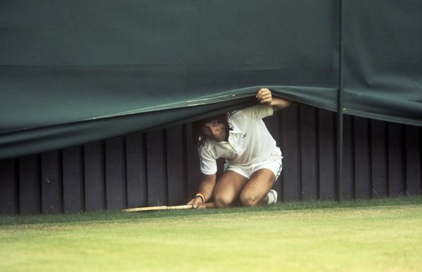 Tennis - Ilie Nastase (Romania) Hides Under The Canopy At The End Of The Court, During The Match. Wimbledon Championships, 1977. Nastase V Alexander Credit : Colorsport / Andrew Cowie
