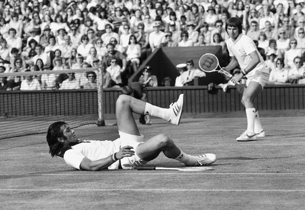 Tennis - 1975 Wimbledon Championships - Men's Doubles Ille Nastase, ground, and Jimmy Connors