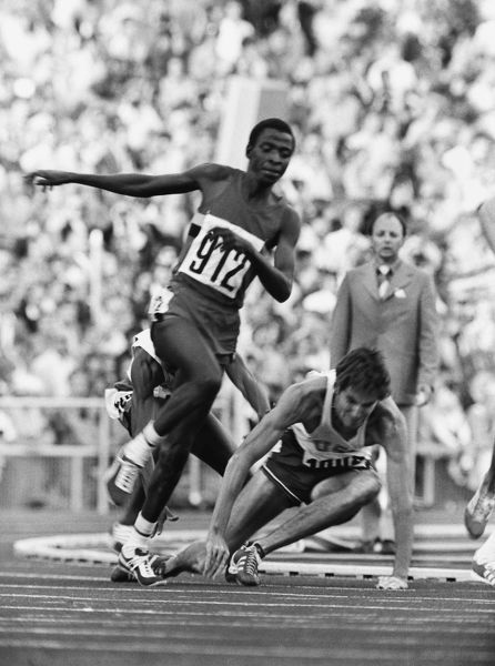 Athletics - 1972 Munich Olympics - Men's 1500m Round One Heat Four Jim Ryun of USA has his heel clipped by Ghana's Billy Fordjour, as Uganda's Vitus Ashaba (#912) runs by with 500 metres to go in the Olympiastadion, Munich, West Germany