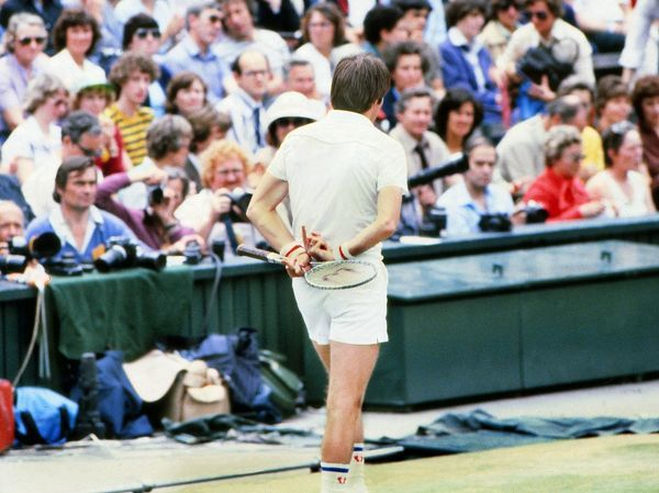 Tennis - 1977 Wimbledon Championships  The USA's Jimmy Connors gives a rude gesture behind his back while talking to the umpire on Centre Court