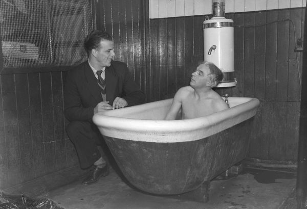 Football - Division Two - Hull City vs. Leeds United Leeds Manager Raich Carter sits in the bath, as John Charles talks over their win over Hull to clinch promotion to Division One