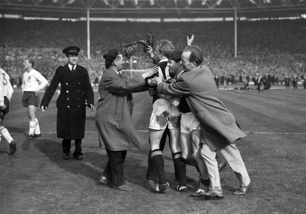 Football - 1963 British Home Championship - England 1 Scotland 2 Scotland players Denis Law (left) and Willie Henderson are mobbed by jubilant supporters after their victory at Wembley Stadium