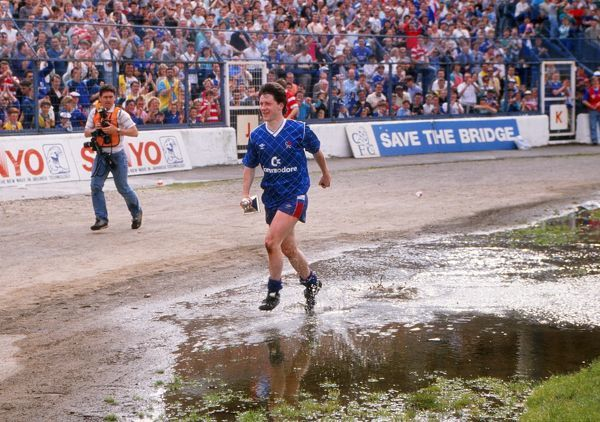 Football - Chelsea v Bradford City Kevin McAllister of Chelsea runs through the puddles of water with the Division Two trophy