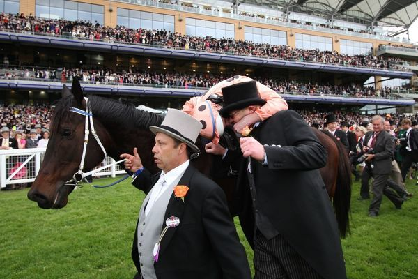 Horse Racing - Royal Ascot - Final Day Jockey Luke Nolan kisses trainer, Peter Moody, while lad, Tony Haydon holds Black Caviar's reigns after winning the Diamond Jubilee Stakes at Royal Ascot