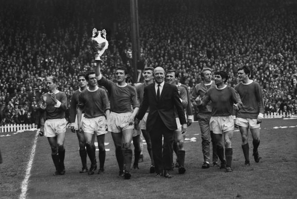 Football - 1966 / 1967 First Division - Manchester United 0 Stoke City 0 The title-winning United team do a lap of honour with the trophy at Old Trafford. Bill Foulkes holds aloft the League Championship trophy with Manager Matt Busby by his side