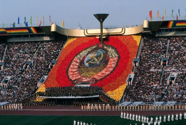 Moscow Olympics 1980 - Opening Ceremony A human wall of cards show the State Emblem of the Soviet Union below the Olympic flame during the ceremony in the Grand Arena, Central Lenin Stadium Area, Moscow, USSR