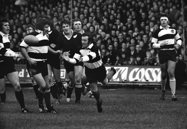 Rugby Union - 1972 / 1973 New Zealand Tour of Great Britain & France - Barbarians 23 New Zealand 11 Phil Bennett passes the ball out for the Barbarians, with teammates Fergus Slattery, far left, and Tom David, with Bob Wilkinson, right, at Cardiff