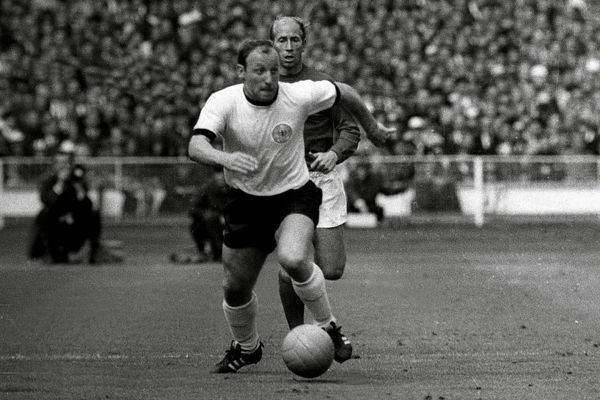 Football - 1966 World Cup Final - England vs. West Germany Uwe Seeler of West Germany on the ball with England's Bobby Charlton behind him at Wembley