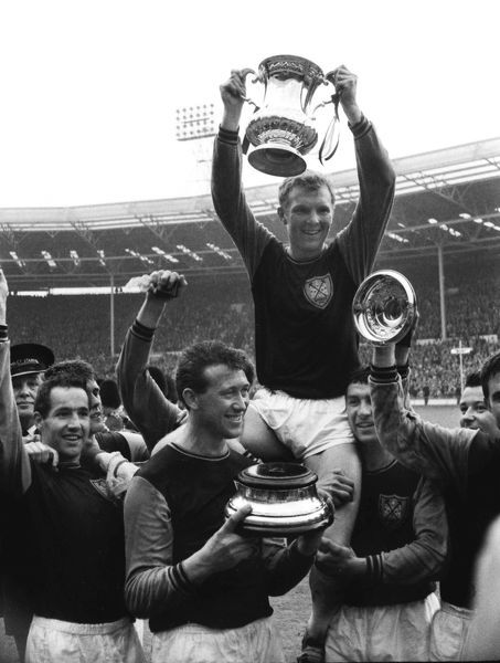 Football - 1964 FA Cup Final - West Ham United 3 Preston North End 2 West Ham captain Bobby Moore is lifted onto his teammates shoulders with the trophy at Wembley.Ken Brown is holding the base of the Cup and Eddie Bovington is left