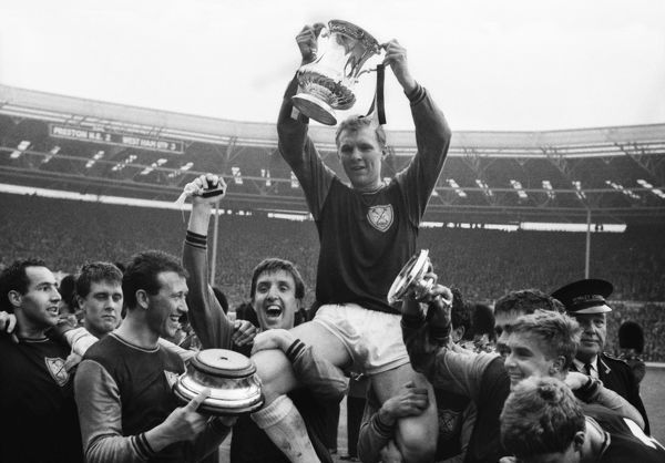 Football - 1964 FA Cup Final - West Ham United 3 Preston North End 2 West Ham United captain Bobby Moore is chaired on his teammates shoulders with the FA Cup trophy after victory at Wembley. Left to right: Eddie Bovington, Geoff Hurst, Ken Brown