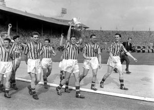 Aston Villa captain Johnny Dixon leads his side on a victory lap with the FA Cup