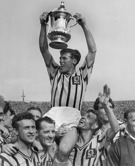 Aston Villa captain Johnny Dixon lifts the FA Cup in 1957