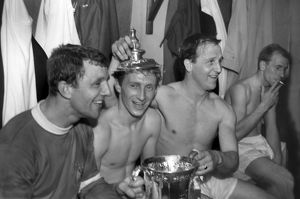 Bobby Charlton has a cigarette as his teammates celebrate after winning the FA Cup.