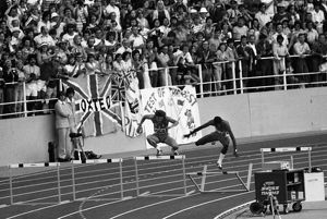Ed Moses clatters into the hudle on his victory lap after winning gold at the 1976