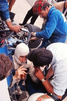 Jackie Stewart has a drink while his mechanics examine the car during practice at
