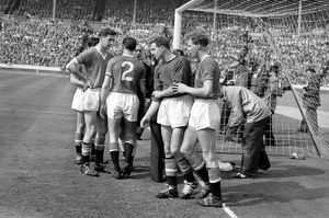 Manchester United goalkeeper Harry Gregg is helped to his feet after his collison