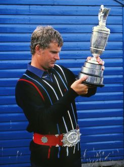 Sandy Lyle examines the Claret Jug while wearing a replica of the original Championship