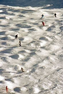 Skiers negotiate a mogul field in Tignes, France in December 1987